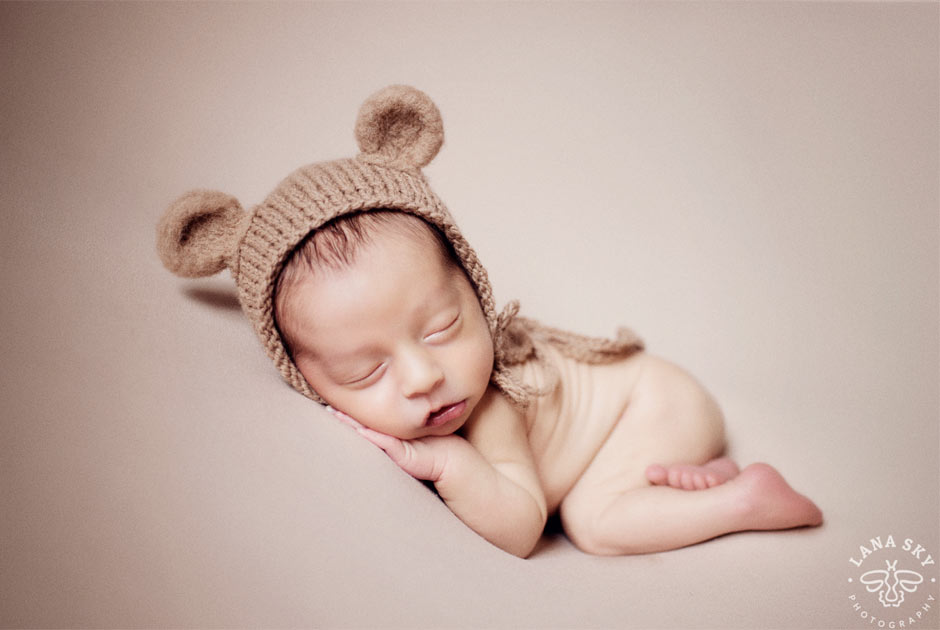 Professional infant portrait of a baby boy in a hat