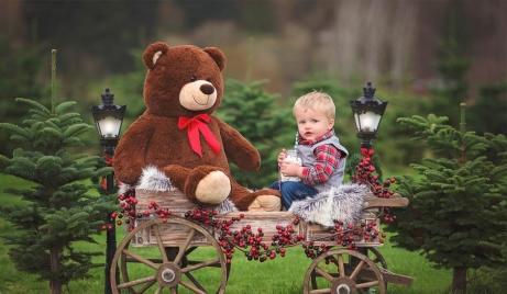 A holiday portrait of a boy with a big Teddy Bear on Christmas tree farm in Redmond, WA