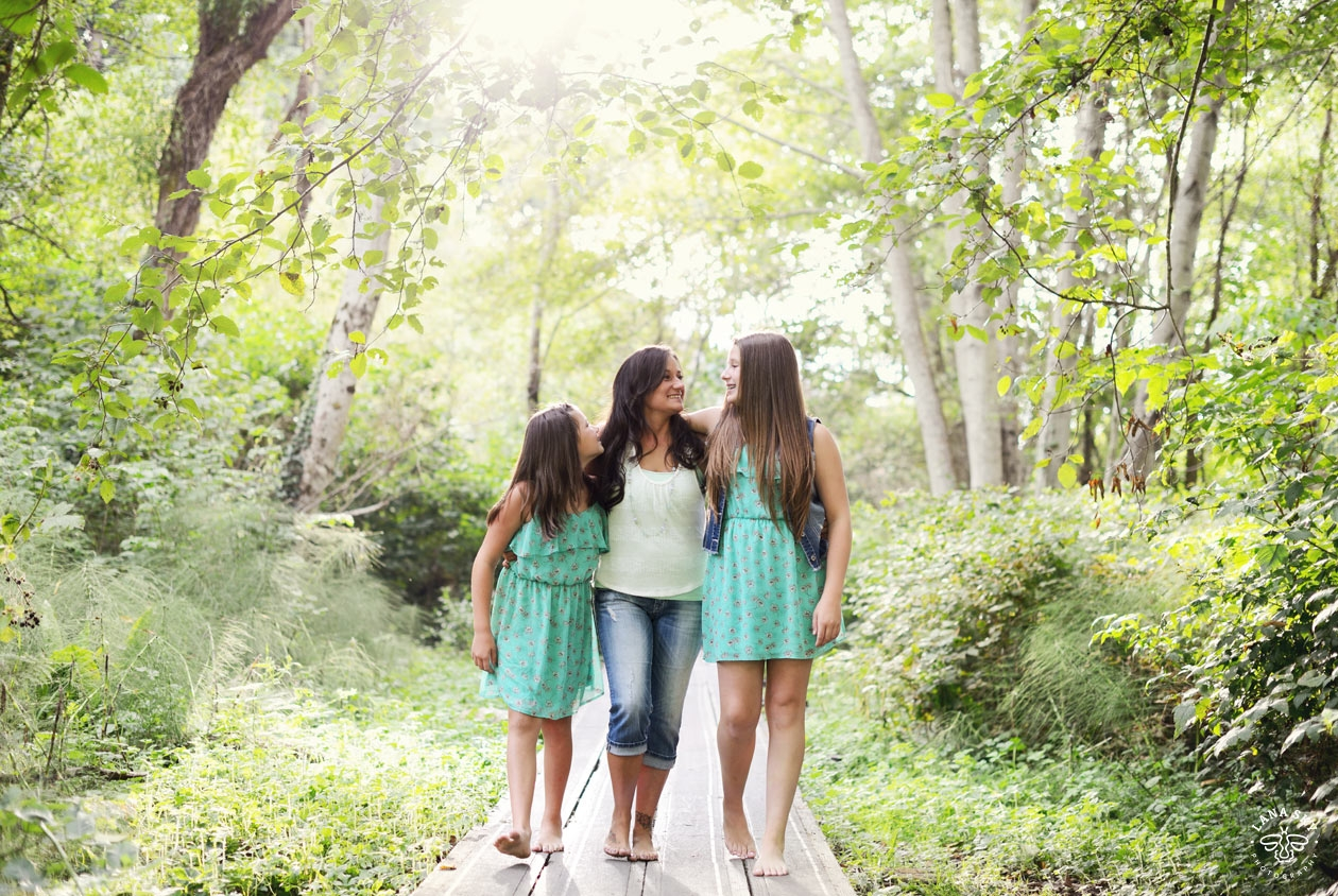 A family portrait, mom and two daughters in a forest