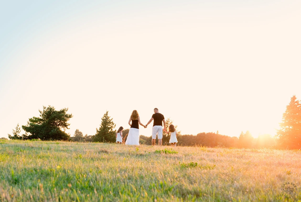 A family portrait on a field during a sunset