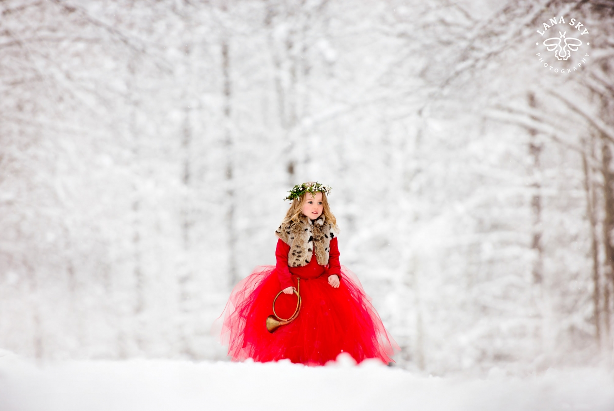 A portrait of a girl in a red dress in a snowy forest