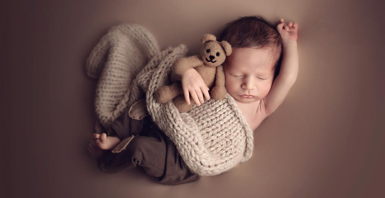 A professional newborn portrait of a boy with a little teddy bear