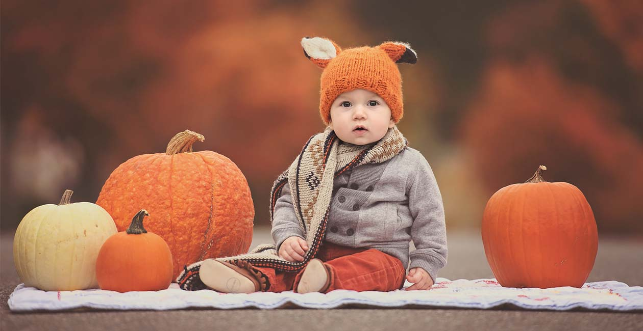 A professional portrait of a boy with pumpkins during fall