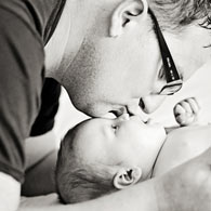 A picture of a father kissing a newborn baby